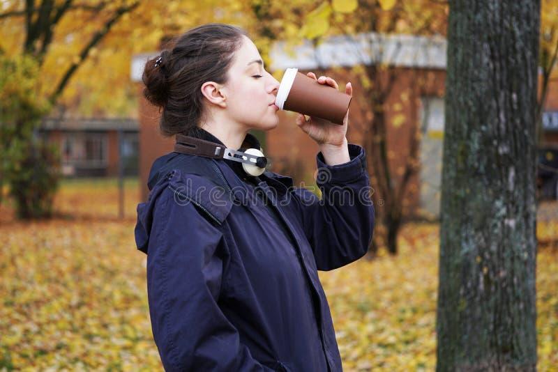Jonge vrouw het drinken koffie om te gaan terwijl het lopen in de herfst royalty-vrije stock foto