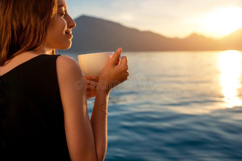 Jonge vrouw het drinken koffie op de pijler bij zonsopgang stock fotografie