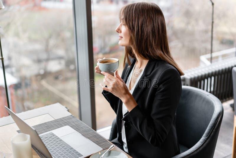 Jonge vrouw het drinken koffie Vrouwelijke holdingskop Het zitten in koffiewinkel bij houten lijst Op lijst is grijs aluminium stock fotografie
