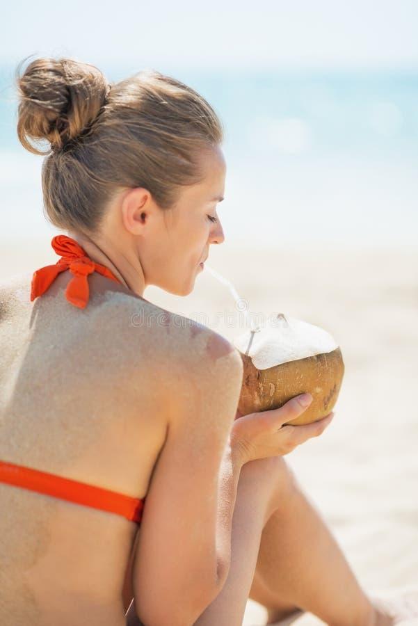 Jonge vrouw het drinken kokosmelk op strand stock foto