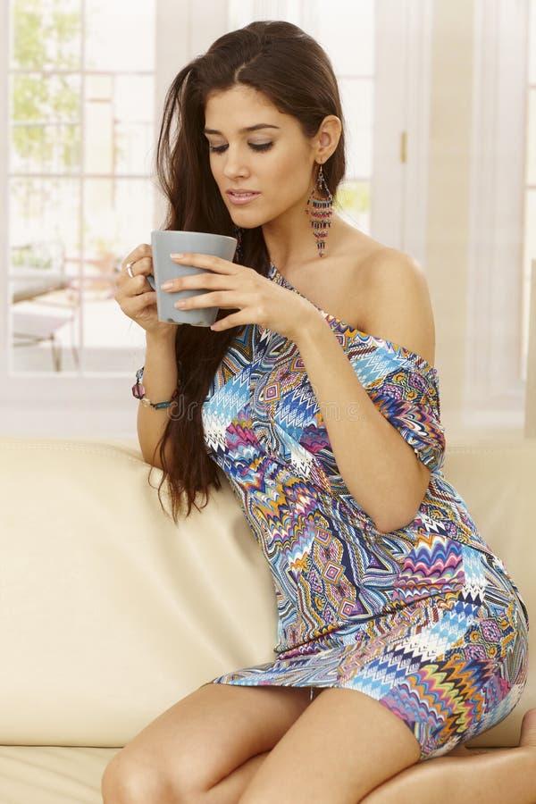 Jonge vrouw het drinken thee thuis stock foto