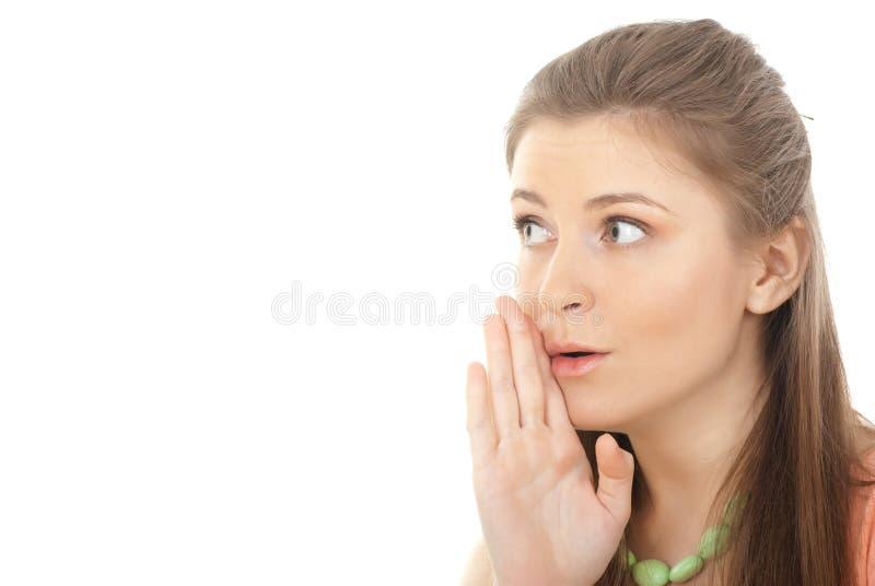 Jonge vrouw het fluisteren roddels stock foto's