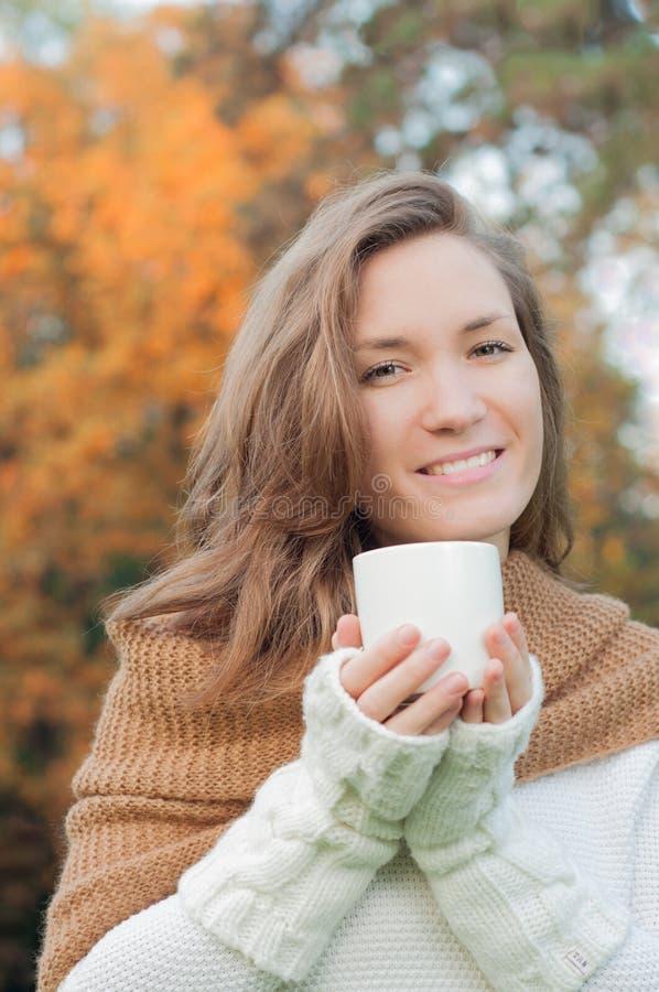 Jonge vrouw het glimlachen holdingskop stock afbeeldingen