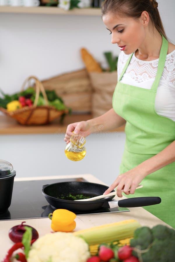 Jonge vrouw in het groene schort koken in de keuken De huisvrouw kookt de maaltijd in een pan stock afbeeldingen