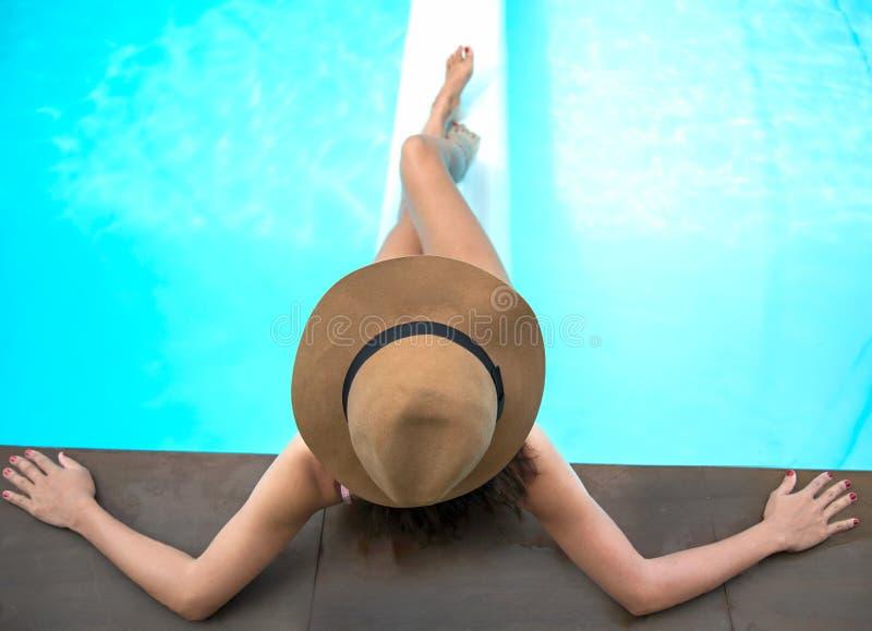 Jonge vrouw in het grote hoed ontspannen op het zwemmen poo royalty-vrije stock foto