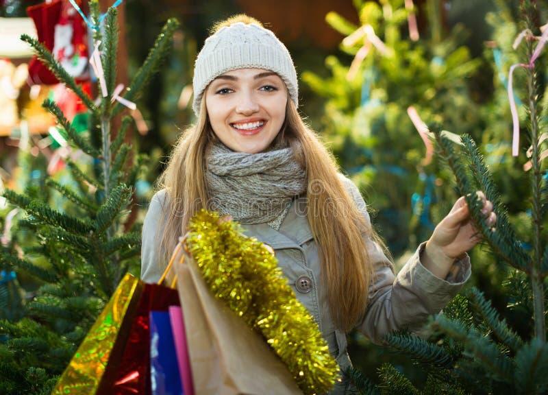Jonge vrouw het kopen Kerstmisboom bij feestelijke markt stock fotografie