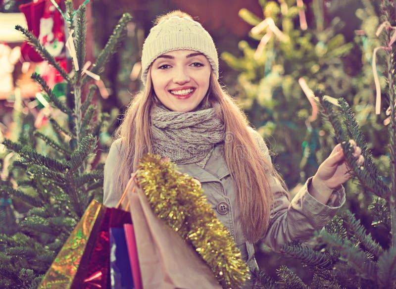 Jonge vrouw het kopen Kerstmisboom bij feestelijke markt royalty-vrije stock foto