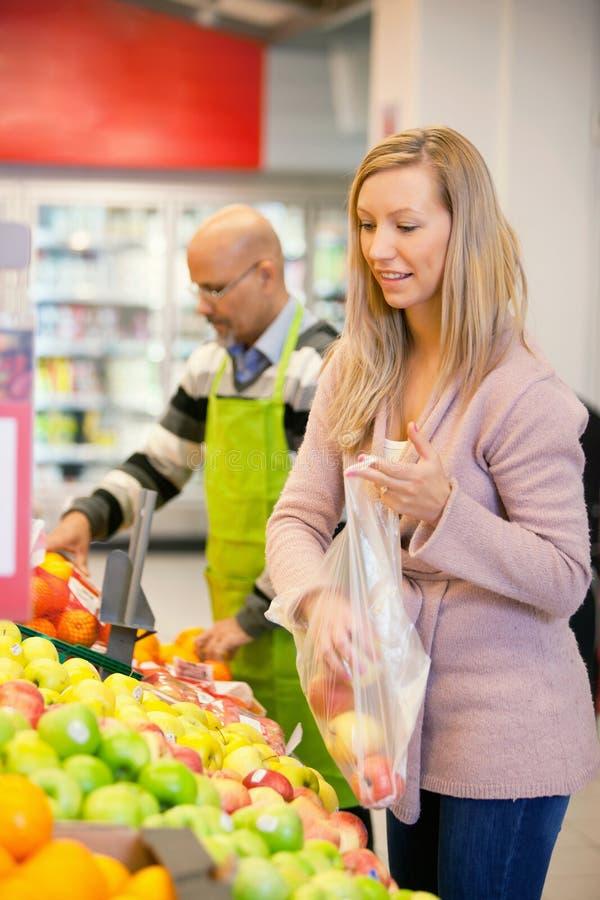Jonge vrouw het kopen vruchten stock afbeelding