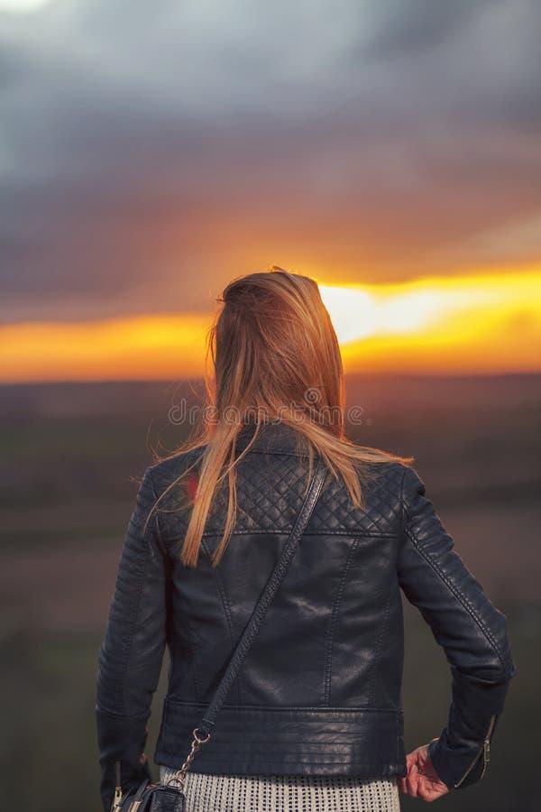 Jonge Vrouw het letten op zon bij alleen zonsondergang stock fotografie