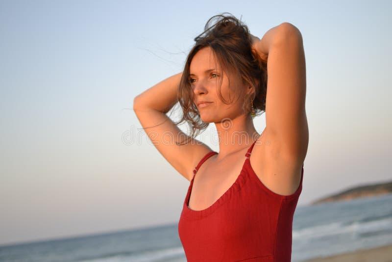 Jonge vrouw het letten op zonsondergang op het strand stock afbeelding