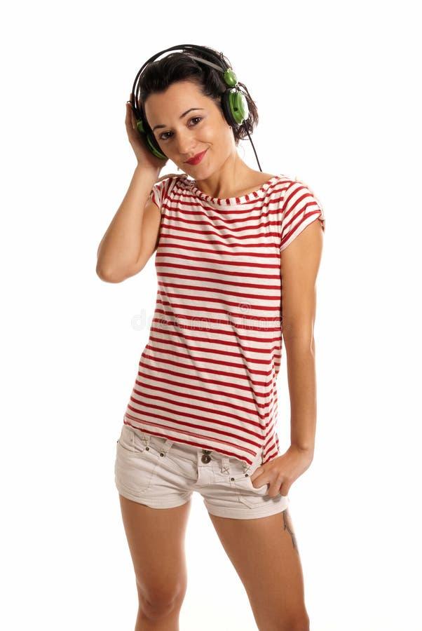 Jonge vrouw het luisteren muziek met hoofdtelefoons die zich op witte achtergrond bevinden stock afbeeldingen