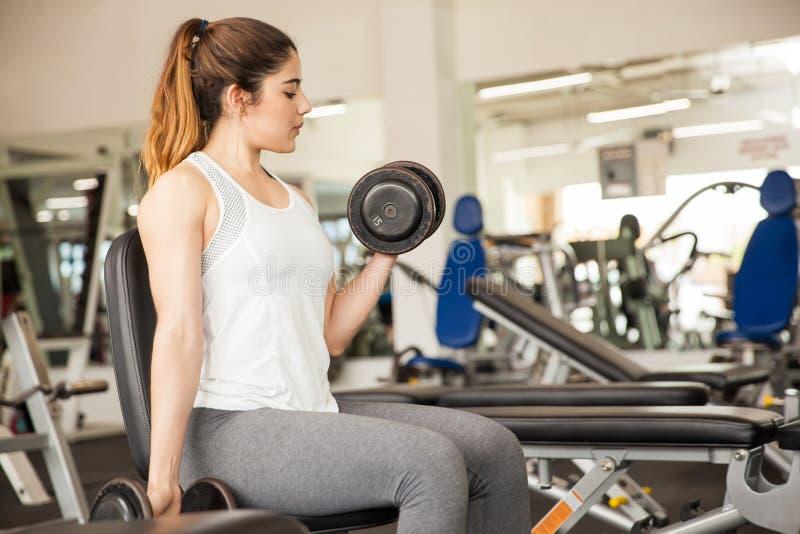 Jonge vrouw het opheffen gewichten bij de gymnastiek stock afbeelding