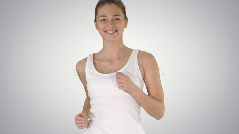 Jonge vrouw in het overhemd die van de gradiënttank op gradiëntachtergrond lopen stock afbeelding