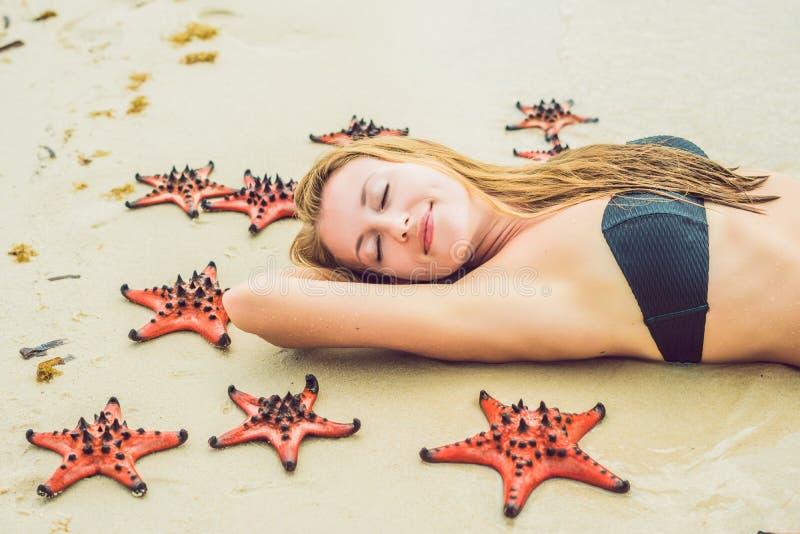 Jonge vrouw in het overzees met rode zeesterren stock foto