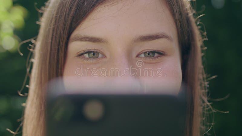 Jonge vrouw in het park die een telefoon met behulp van royalty-vrije stock foto