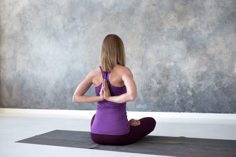 Jonge vrouw het praktizeren yoga, die met Namaste achter haar zitten achter, het uitwerken stock afbeelding