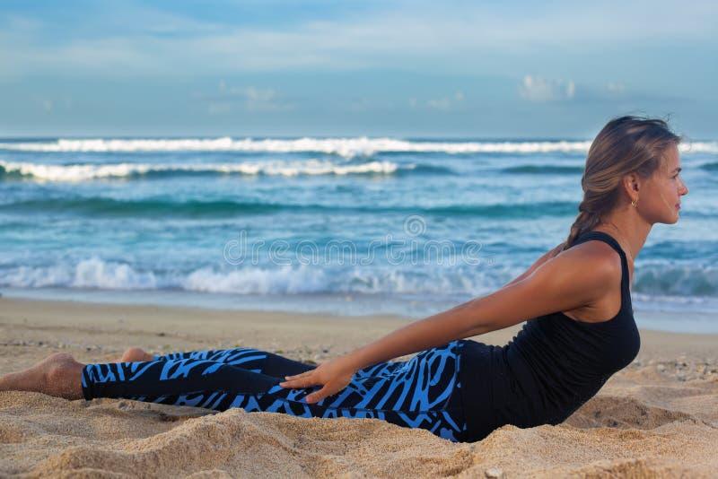 Jonge vrouw het praktizeren yoga op het strand bij zonsopgang royalty-vrije stock afbeeldingen