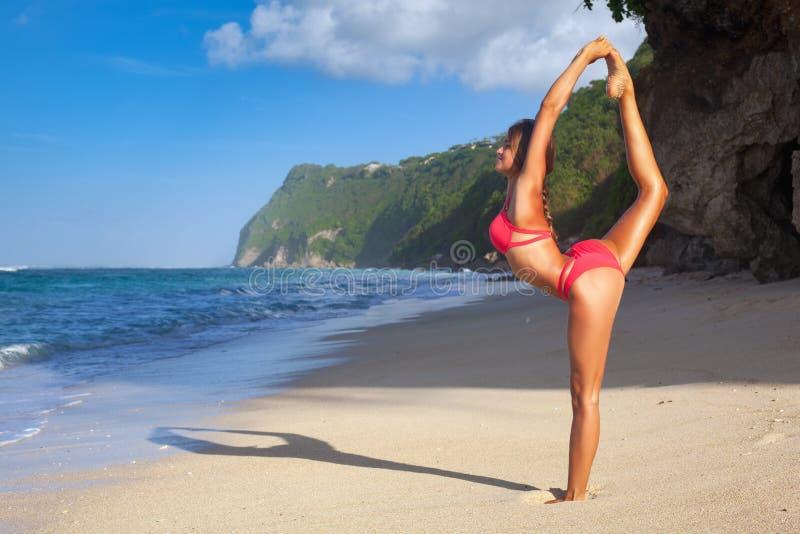 Jonge vrouw het praktizeren yoga op het strand bij zonsopgang stock fotografie