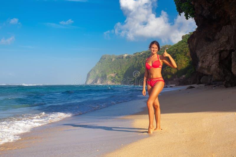 Jonge vrouw het praktizeren yoga op het strand bij zonsopgang stock foto's