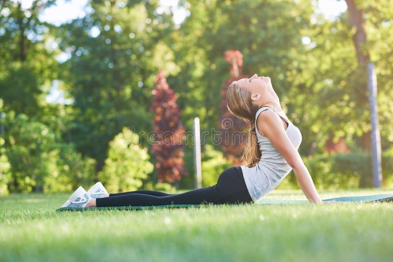 Jonge vrouw het praktizeren yoga in openlucht bij het park royalty-vrije stock foto