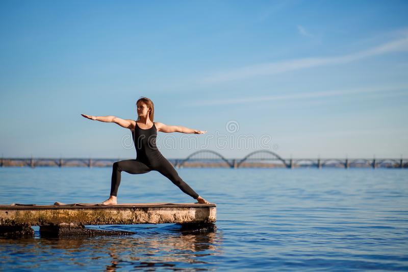 Jonge vrouw het praktizeren yogaoefening bij stille houten pijler met stadsachtergrond Sport en recreatie in stadsstormloop stock afbeelding