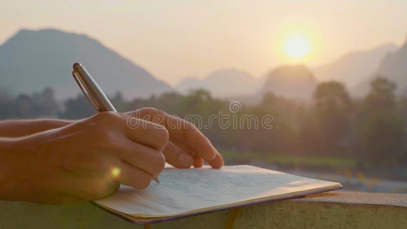 Jonge vrouw het schrijven ochtendpagina's in agenda openlucht, close-up royalty-vrije stock fotografie