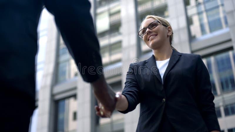 Jonge vrouw het schudden hand met werkgever, gelukwensen op het huren of bevordering royalty-vrije stock fotografie