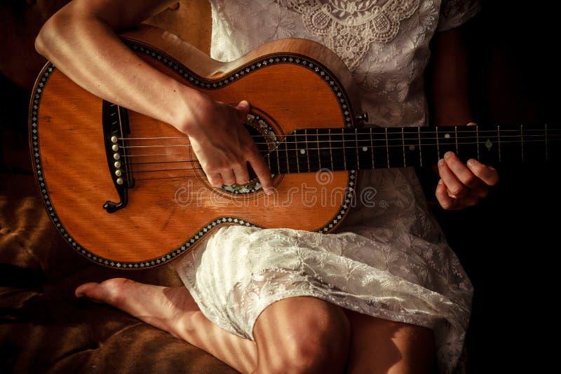 Jonge vrouw het spelen gitaar met schaduwen van jaloezies royalty-vrije stock afbeeldingen