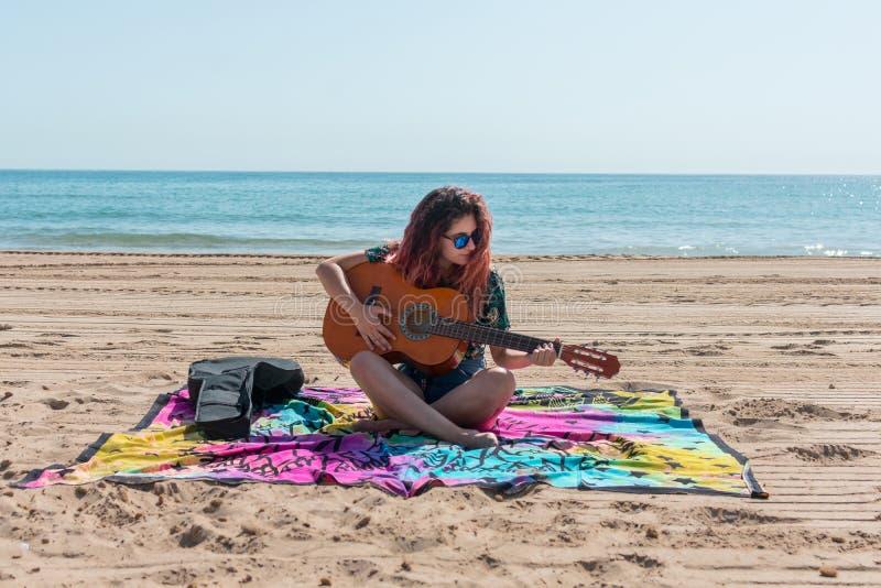 Jonge vrouw het spelen gitaar op het strand royalty-vrije stock afbeelding