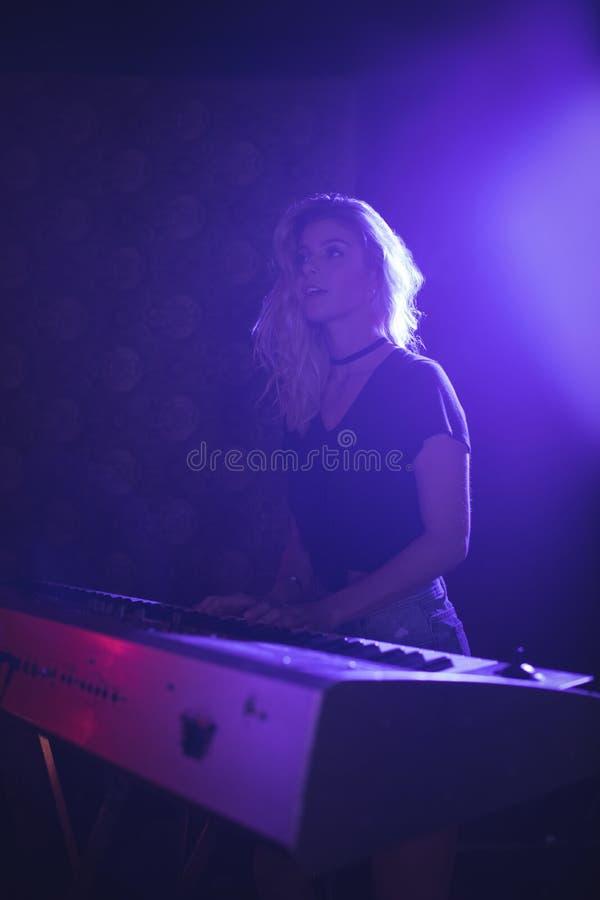 Jonge vrouw het spelen piano op verlicht stadium in nachtclub royalty-vrije stock foto's