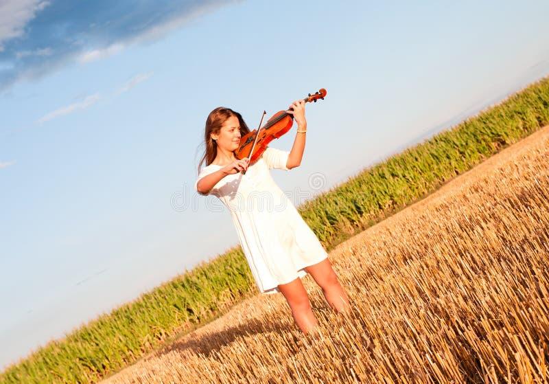 Jonge vrouw het spelen viool in openlucht stock fotografie