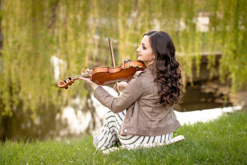 Jonge vrouw het spelen viool in het park dichtbij water stock afbeelding