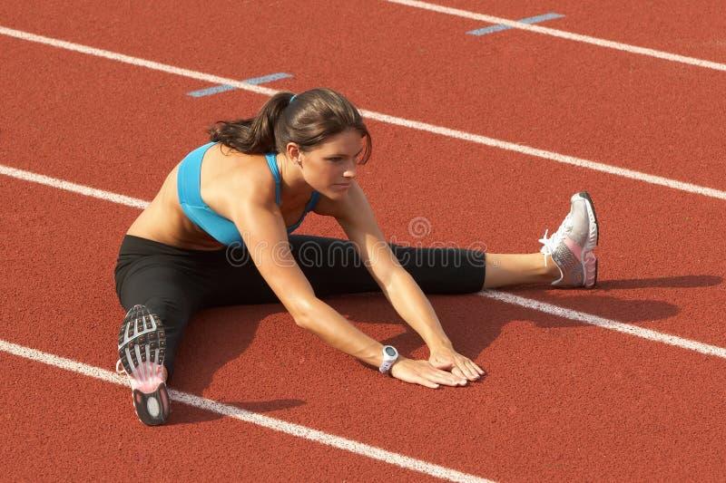 Jonge Vrouw in het Uitrekken zich van de Bustehouder van Sporten Benen op Spoor stock afbeeldingen