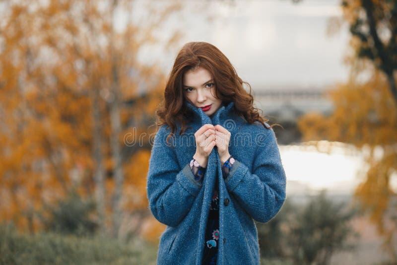 In jonge vrouw in het warme blauwe laag stellen in het de herfstpark Zij die de laag sluiten door haar handen royalty-vrije stock afbeelding