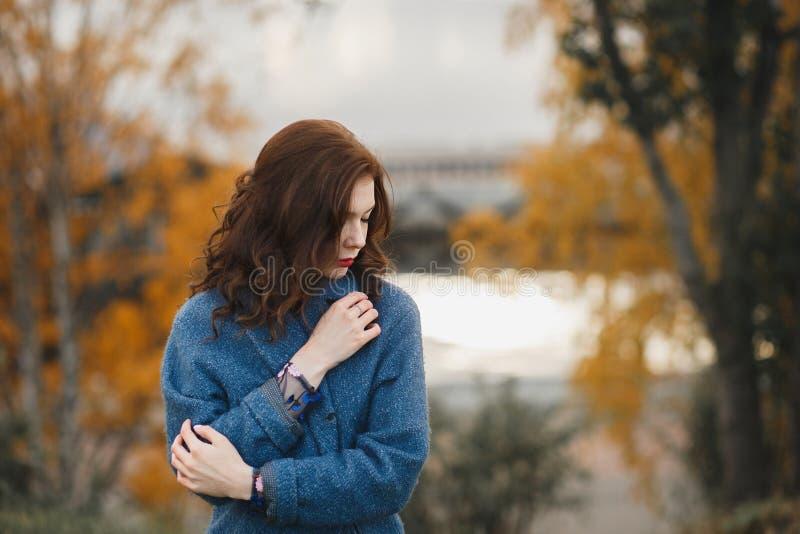 In jonge vrouw in het warme blauwe laag stellen in het de herfstpark Zij die de laag sluiten door haar handen stock afbeeldingen