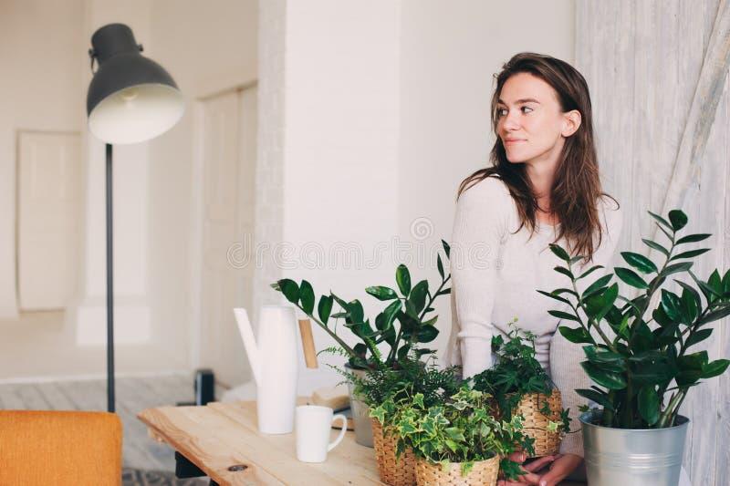Jonge vrouw het water geven bloempotten thuis Toevallige levensstijlreeks in modern Skandinavisch binnenland stock fotografie