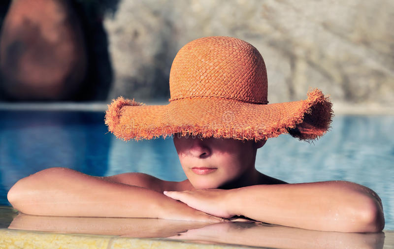 Jonge vrouw in hoed die door de kant van pool rust royalty-vrije stock afbeelding