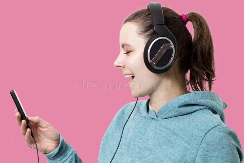 Jonge vrouw in hoofdtelefoons met speler die in die handen aan popmuziek luisteren op roze achtergrond wordt geïsoleerd Luister a royalty-vrije stock foto's