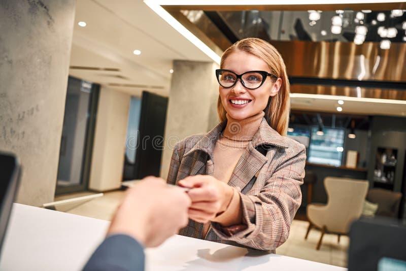 Jonge vrouw in hotelcontrole binnen op ontvangst of voorkantoor die zeer belangrijke kaart worden gegeven royalty-vrije stock fotografie