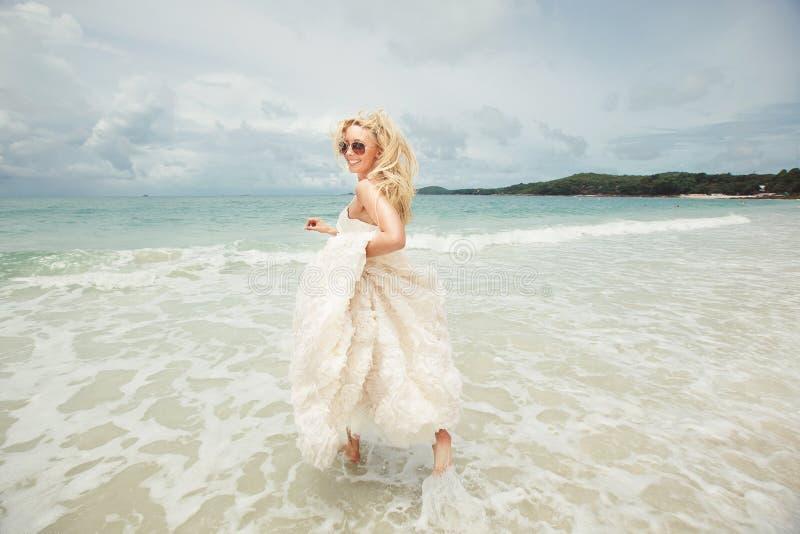 Jonge vrouw in huwelijkskleding die over overzees lopen die terugkeren gelukkige en grappige bruid op het strand stock foto