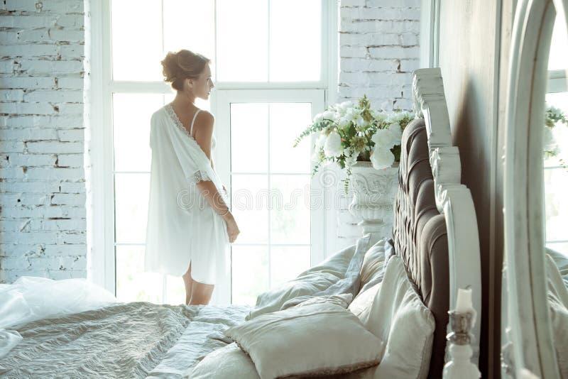 Jonge vrouw in kantlingerie die zich voor reusachtig venster bevinden royalty-vrije stock afbeelding