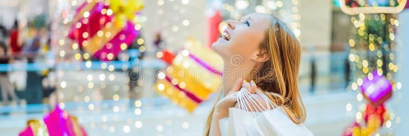 Jonge vrouw in Kerstmiswandelgalerij met Kerstmis het winkelen De schoonheid koopt Kerstnacht het winkelen kortingenbanner, LANG  royalty-vrije stock afbeelding