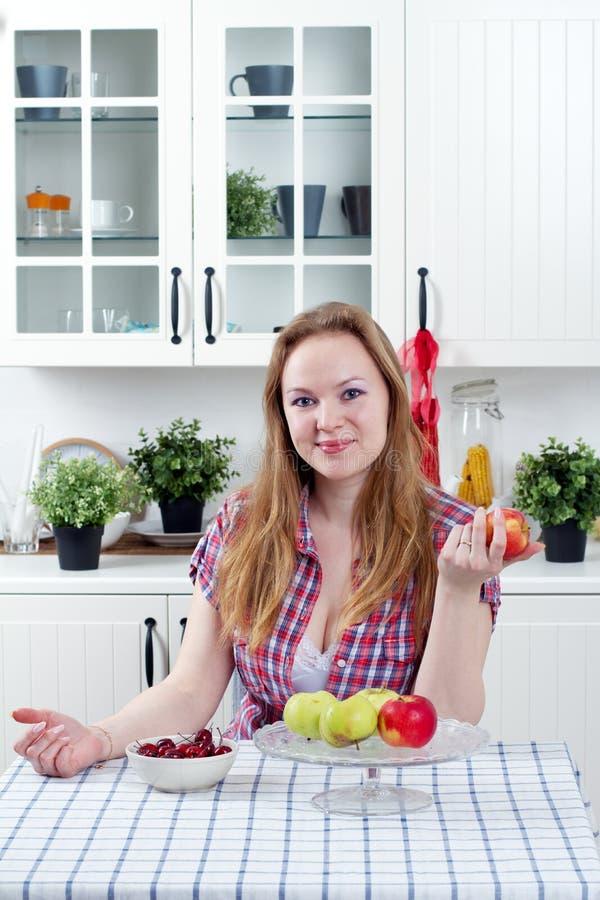 Jonge vrouw in keuken stock afbeeldingen