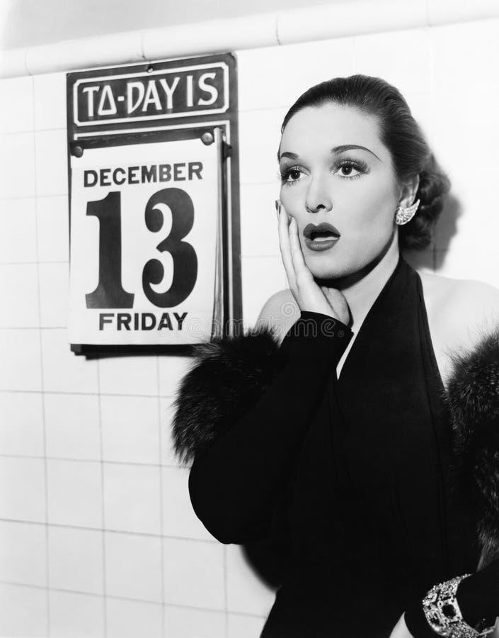 Jonge vrouw kijken die die na het zien van Vrijdag wordt geschokt dertiende op een kalender (Alle afgeschilderde personen leven n royalty-vrije stock foto
