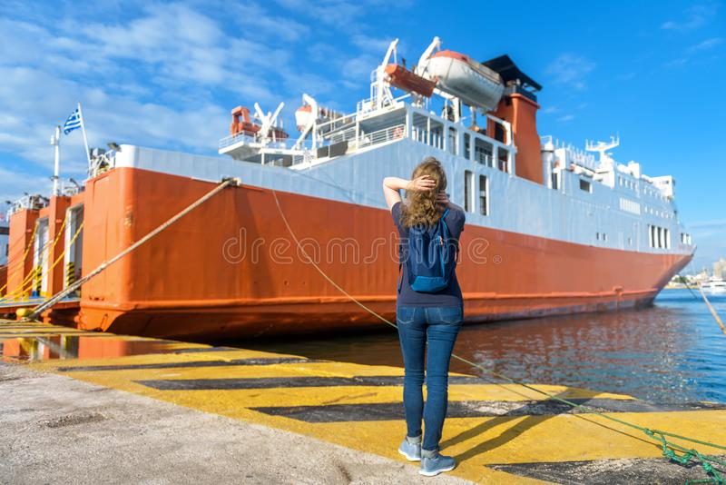 Jonge vrouw kijkt naar een veerboot in de haven van Piraeus bij Athene, Griekenland stock afbeelding