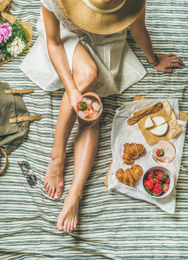 Jonge vrouw in kledingszitting met wijn en snacks stock fotografie
