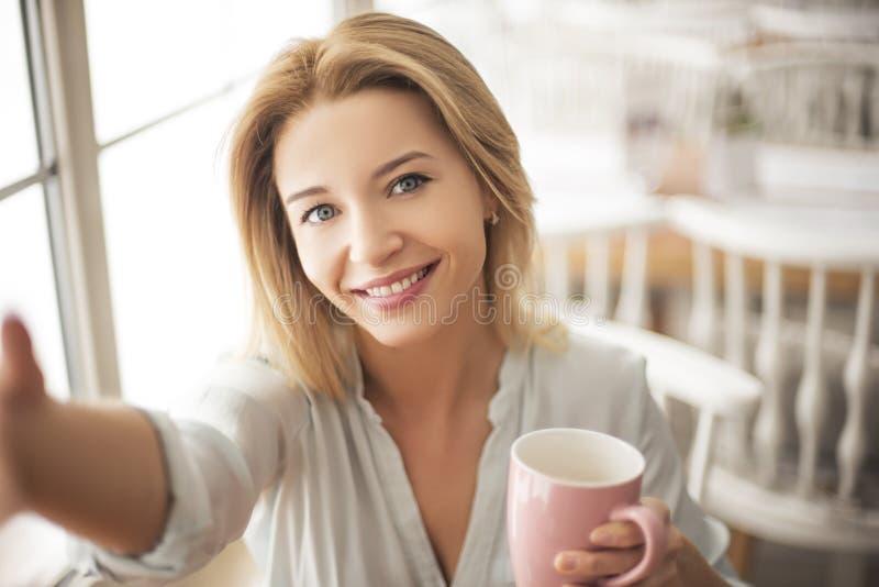 Jonge vrouw in koffiezitting met kop die van koffie selfie foto's op smartphone gelukkig close-up nemen stock afbeelding