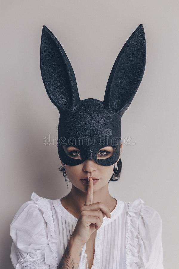 Jonge vrouw in konijntjesmasker die stil teken tonen royalty-vrije stock foto's