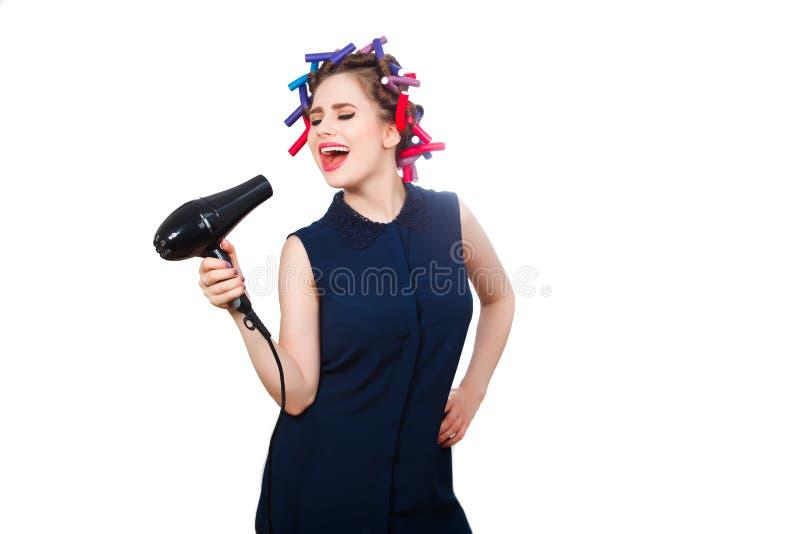 Jonge vrouw in krulspeld die expressively zingen Geïsoleerde stock foto's