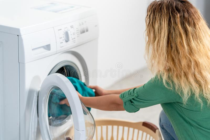 Jonge vrouw, laad de wasmachine voor het reinigen van wasdrogers royalty-vrije stock fotografie